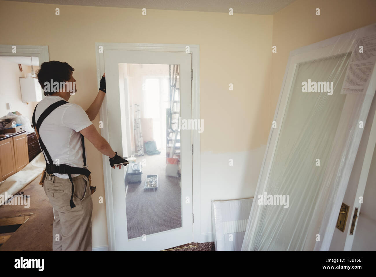 Carpenter fixing a door & Carpenter fixing a door Stock Photo: 122576983 - Alamy