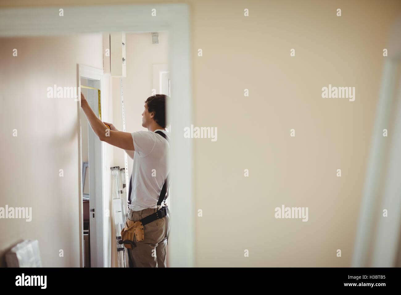Carpenter measuring a door frame Stock Photo: 122577145 - Alamy