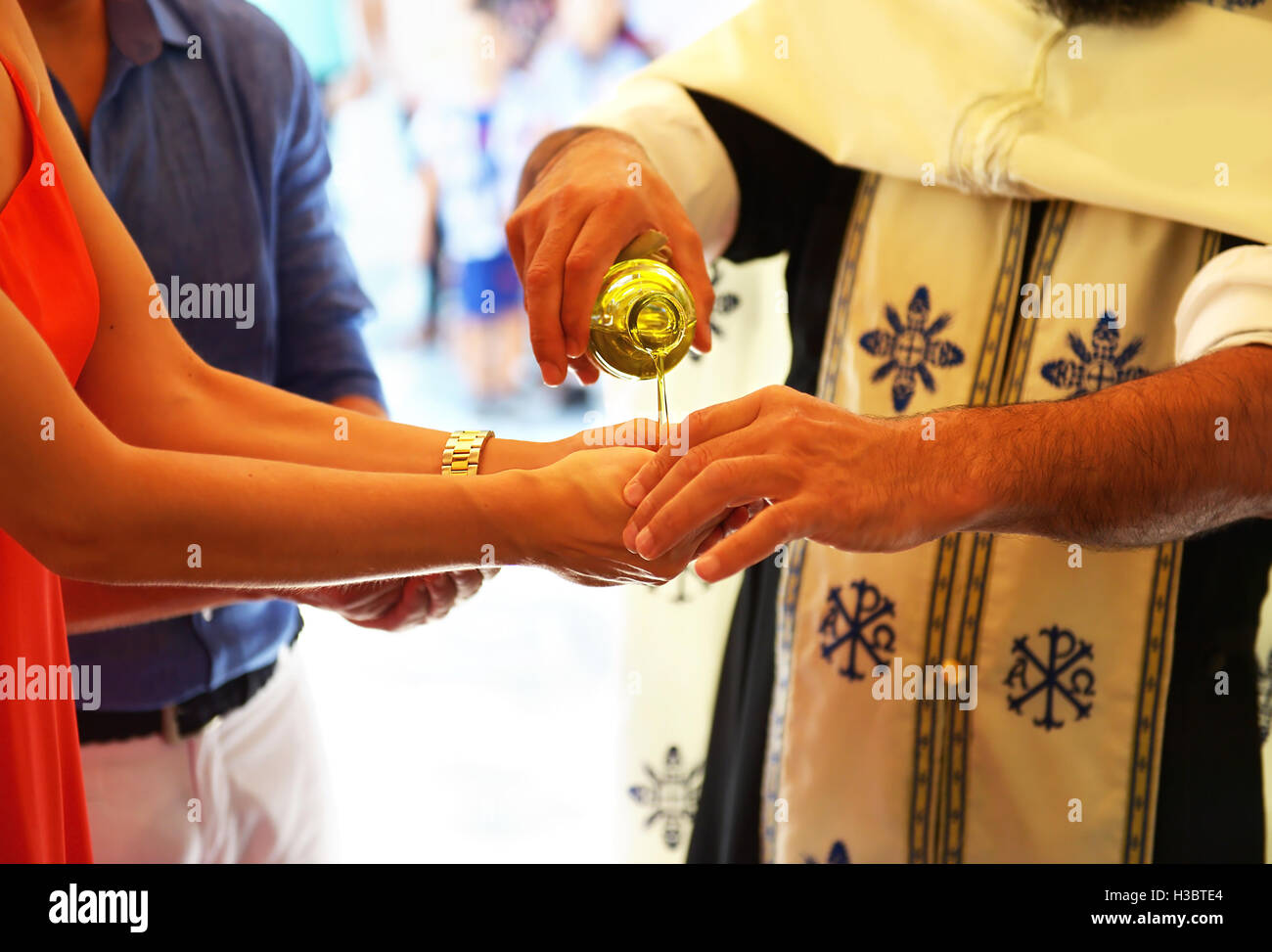 priest puts the baptism oil on the hand of godmother - Stock Image