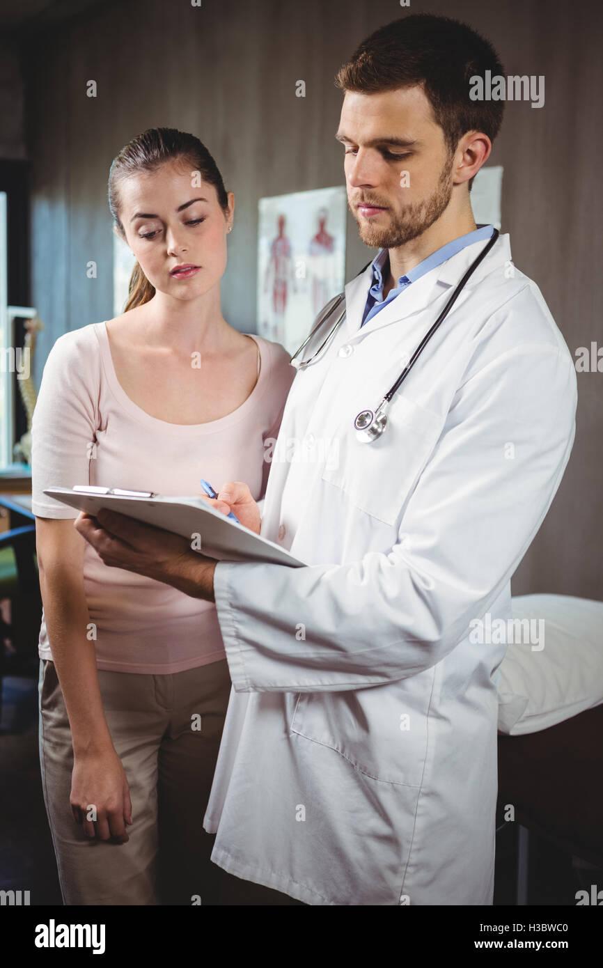 Physiotherapist explaining diagnosis to female patient - Stock Image