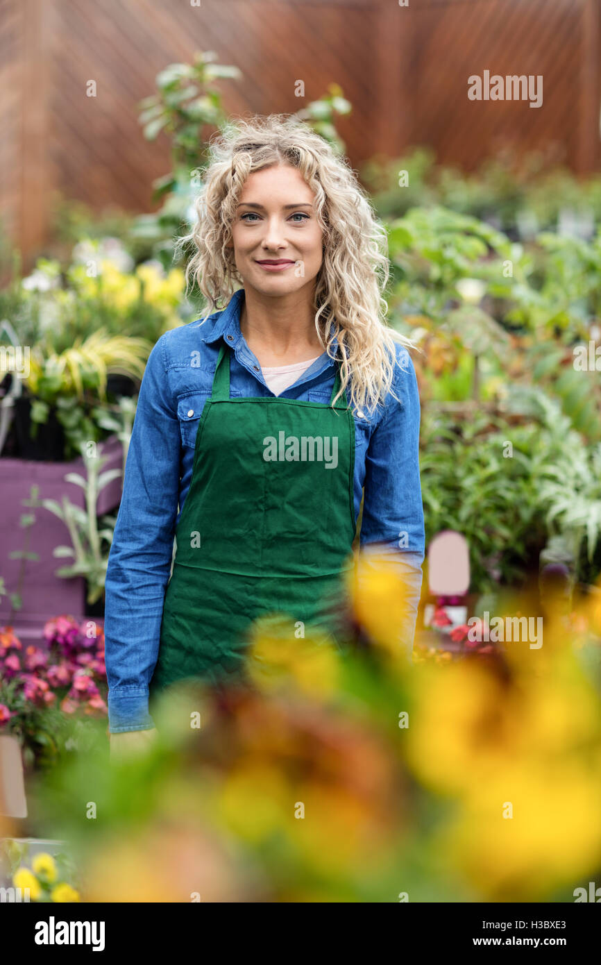 Portrait of female florist smiling - Stock Image