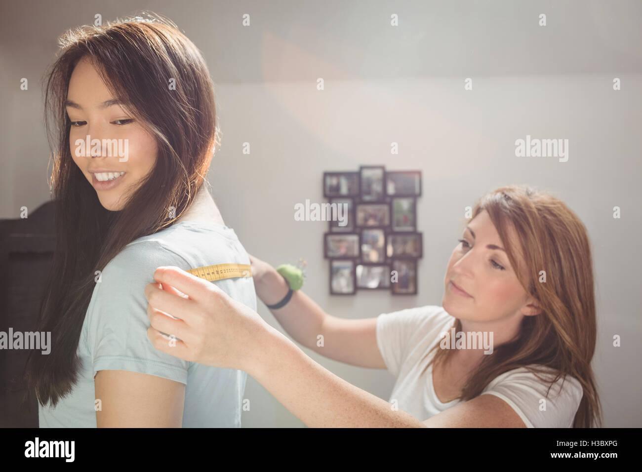 Fashion designer measuring woman's shoulders Stock Photo