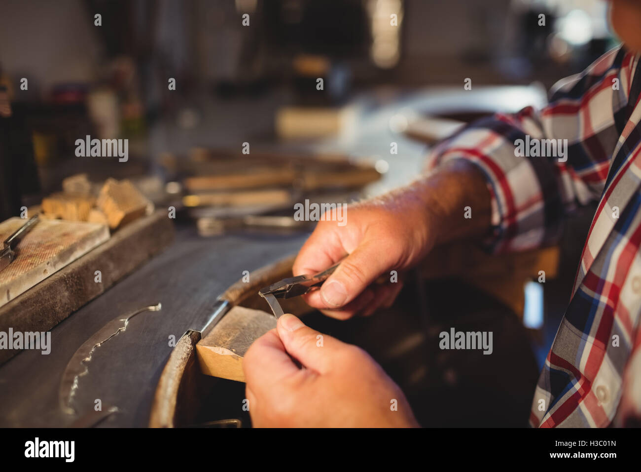 Goldsmith shaping metal with pilers - Stock Image