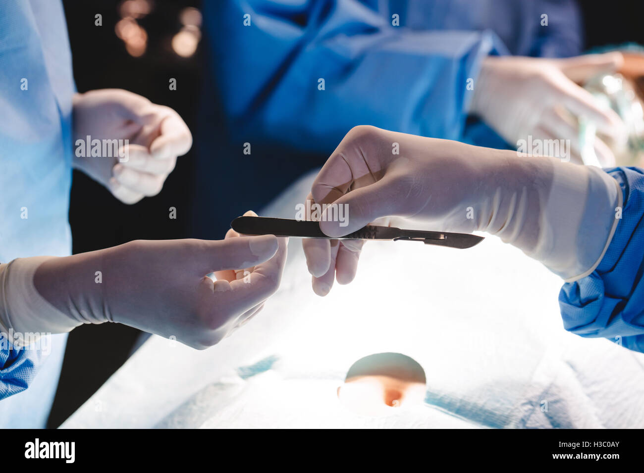 Surgeons giving operation blade to colleague in operation room - Stock Image