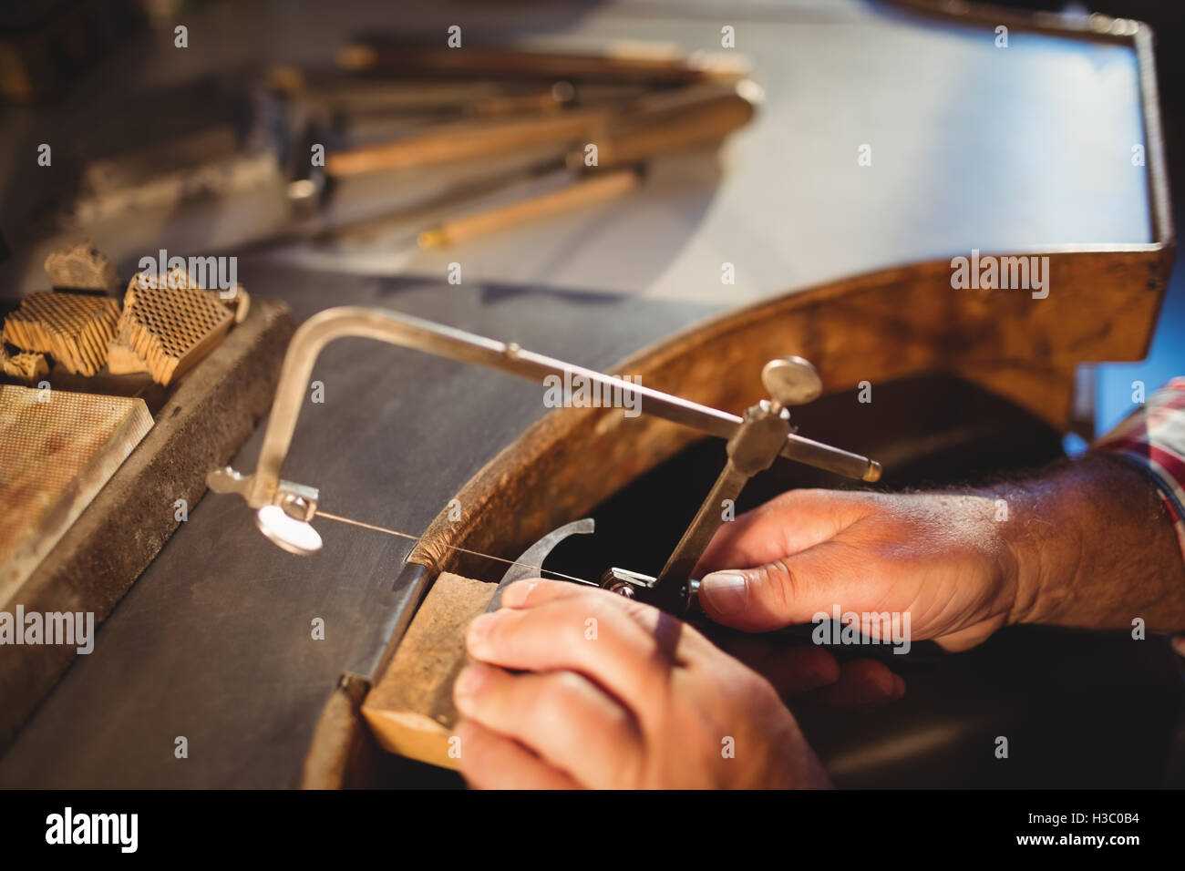 Goldsmith shaping metal with coping saw - Stock Image
