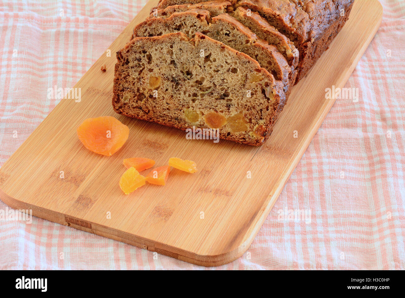 Fresh baked banana bread with sweet apricot pieces in horizontal format - Stock Image