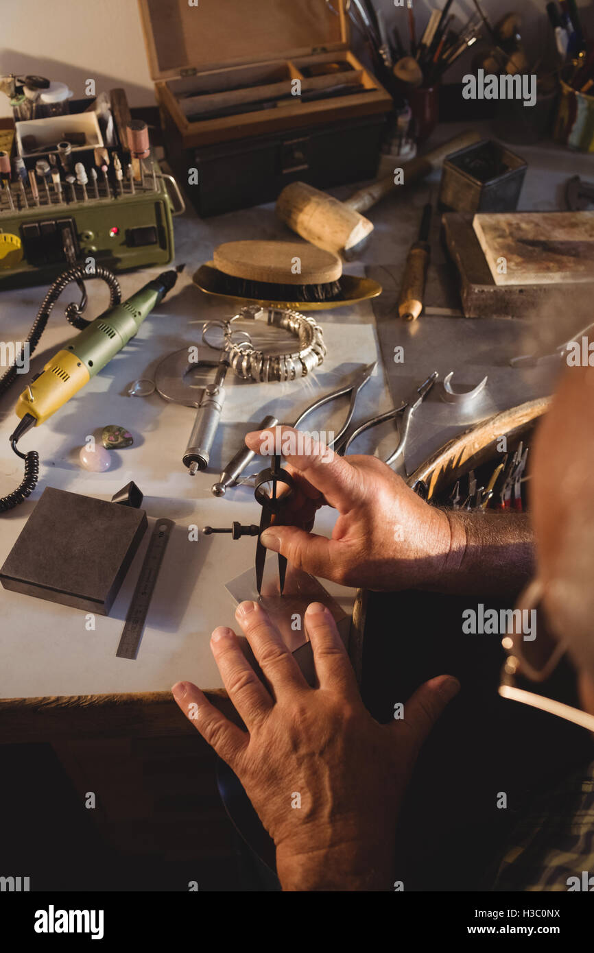 Goldsmith working with divider compass - Stock Image