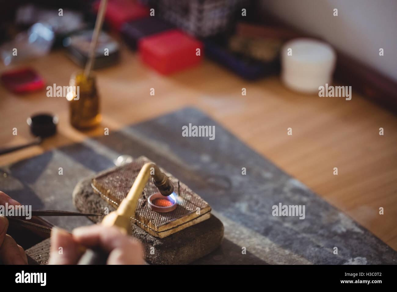 Goldsmith crafting ring by burner Stock Photo