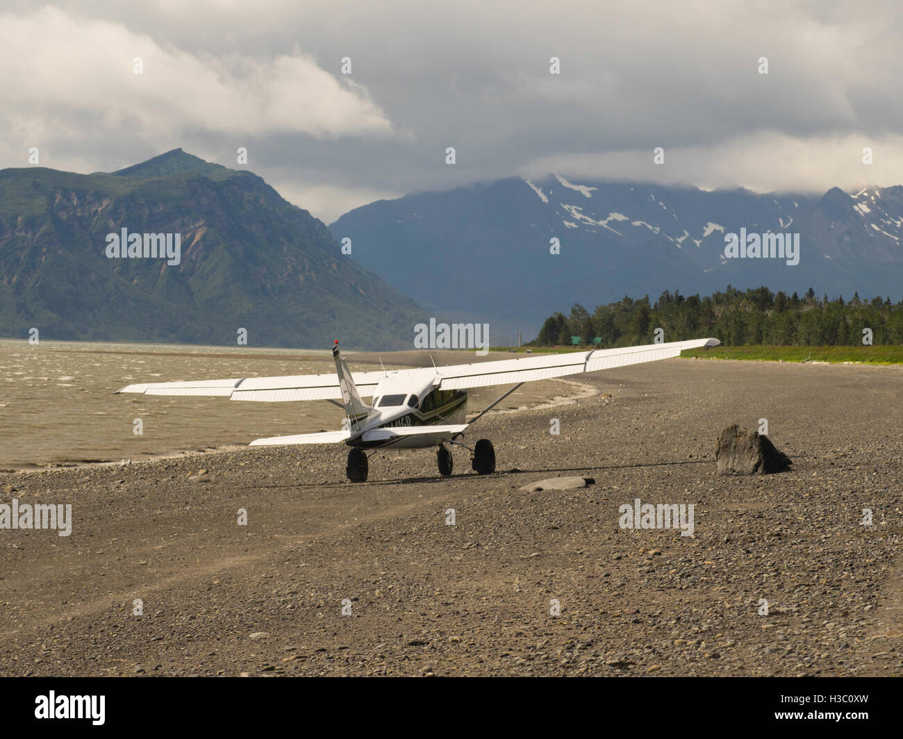 A bush plane takes off from the shore of Chinitna Bay, Lake Clark National Park, Alaska. - Stock Image