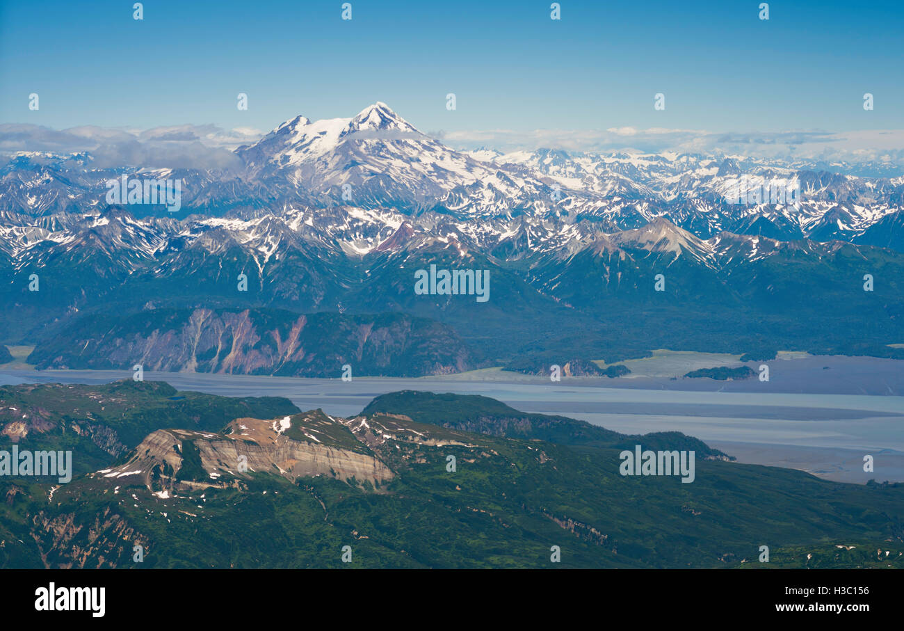 Aerial view of the Redoubt Volcano, shrouded in the clouds, with Tuxedni Bay in the foreground, Lake Clark National - Stock Image
