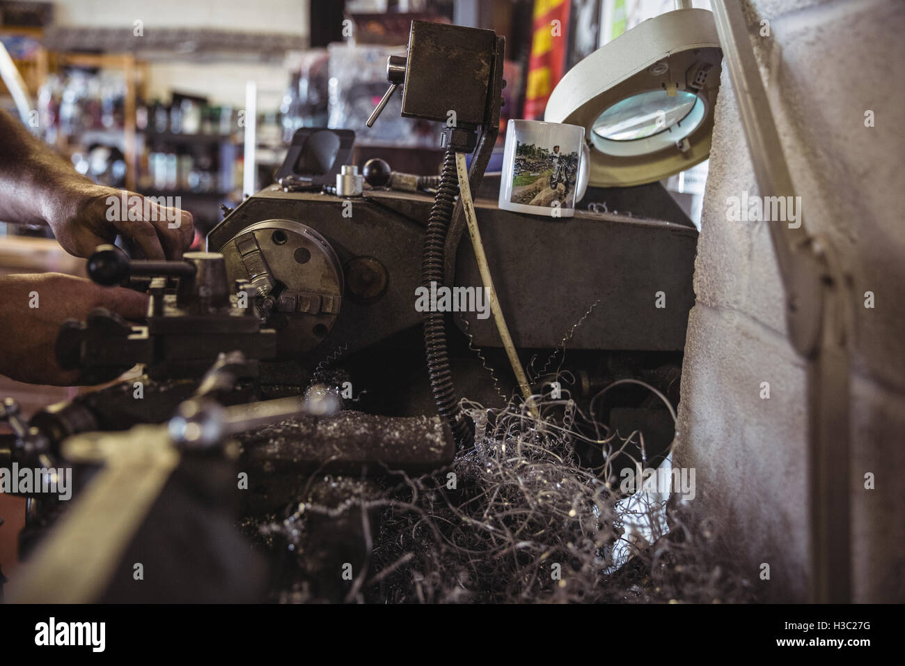 Mechanic working on a lathe machine - Stock Image