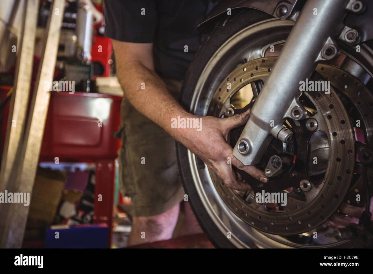 Mechanic examining a motorbike disc brake - Stock Image