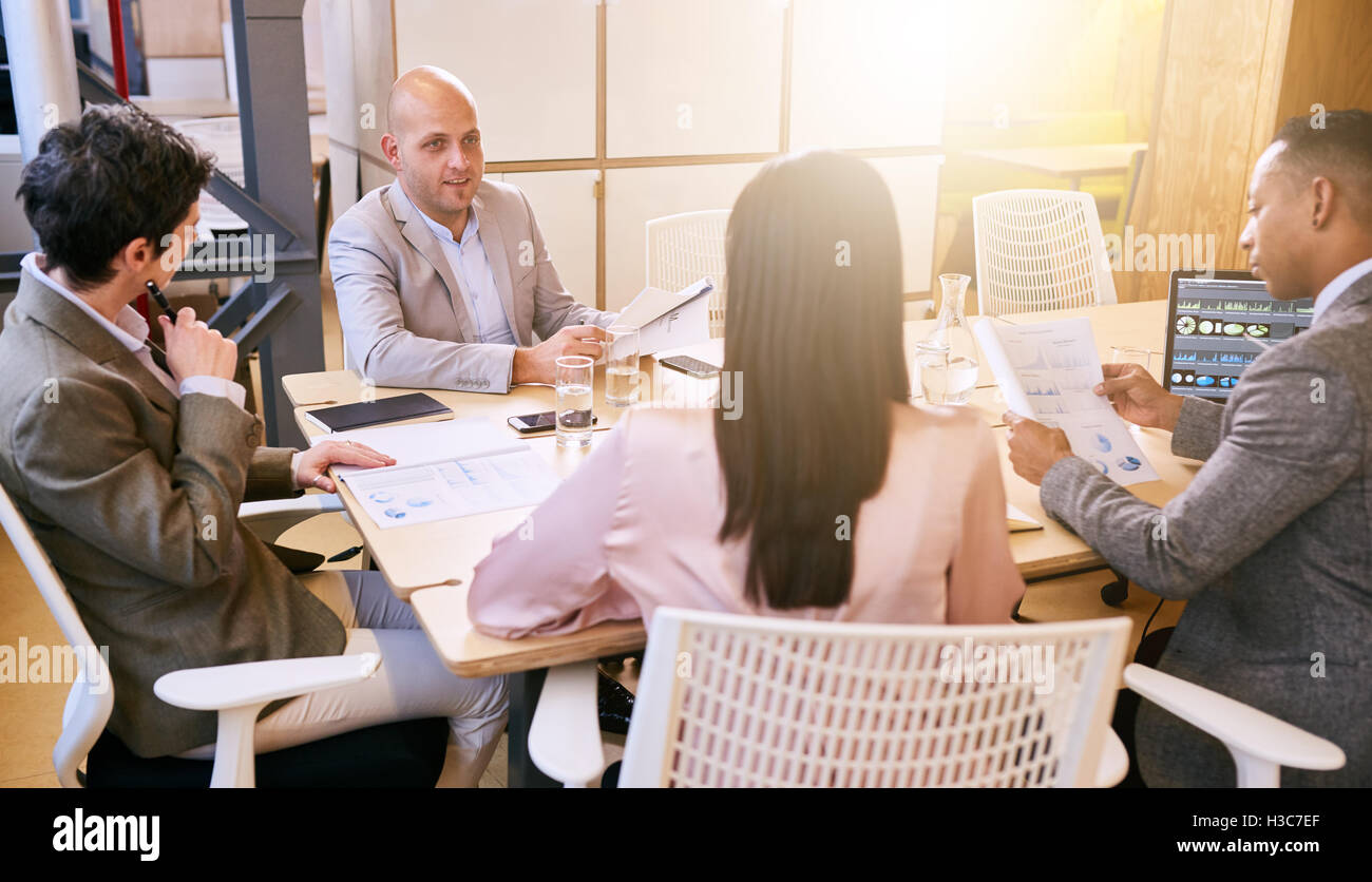 Business meeting between four professional entrepreneurial executives indoors - Stock Image
