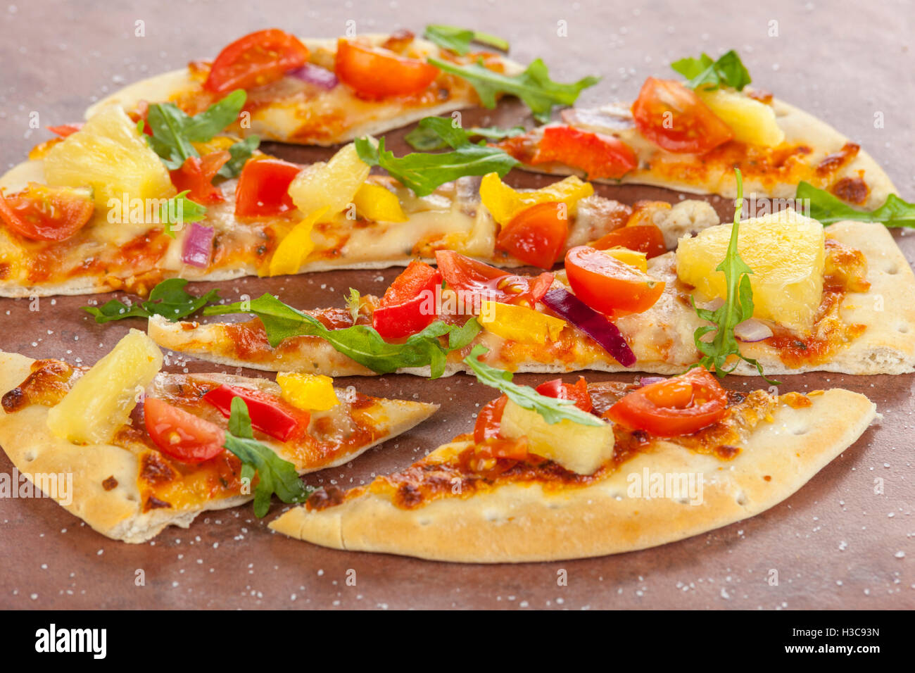 Stone baked thin crust pizza with pineapple, pepper and red onions sprinkled with sea salt and rocket leaves - Stock Image