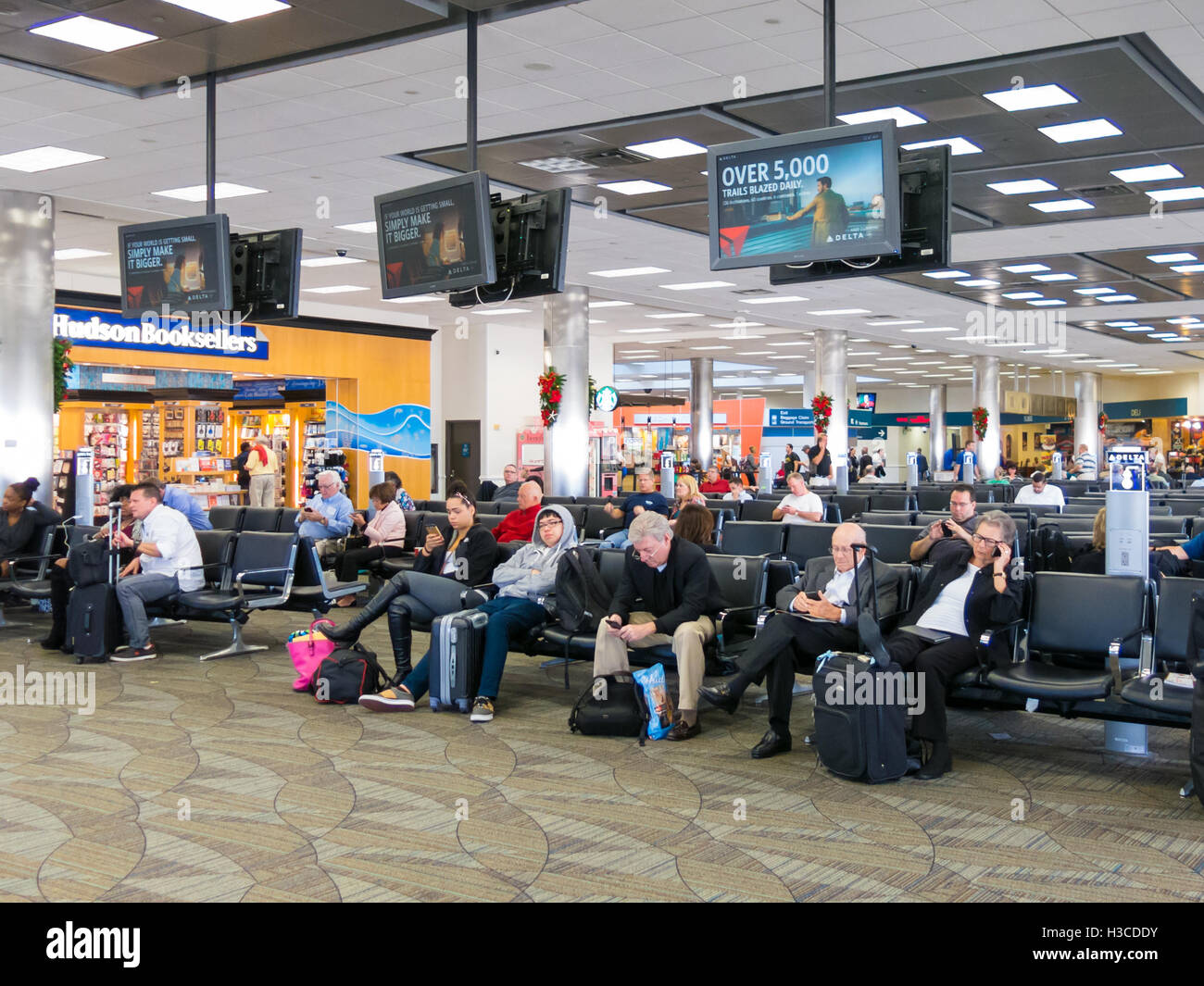 People sitting and waiting on Fort Lauderdale Hollywood International Airport in Florida, USA - Stock Image