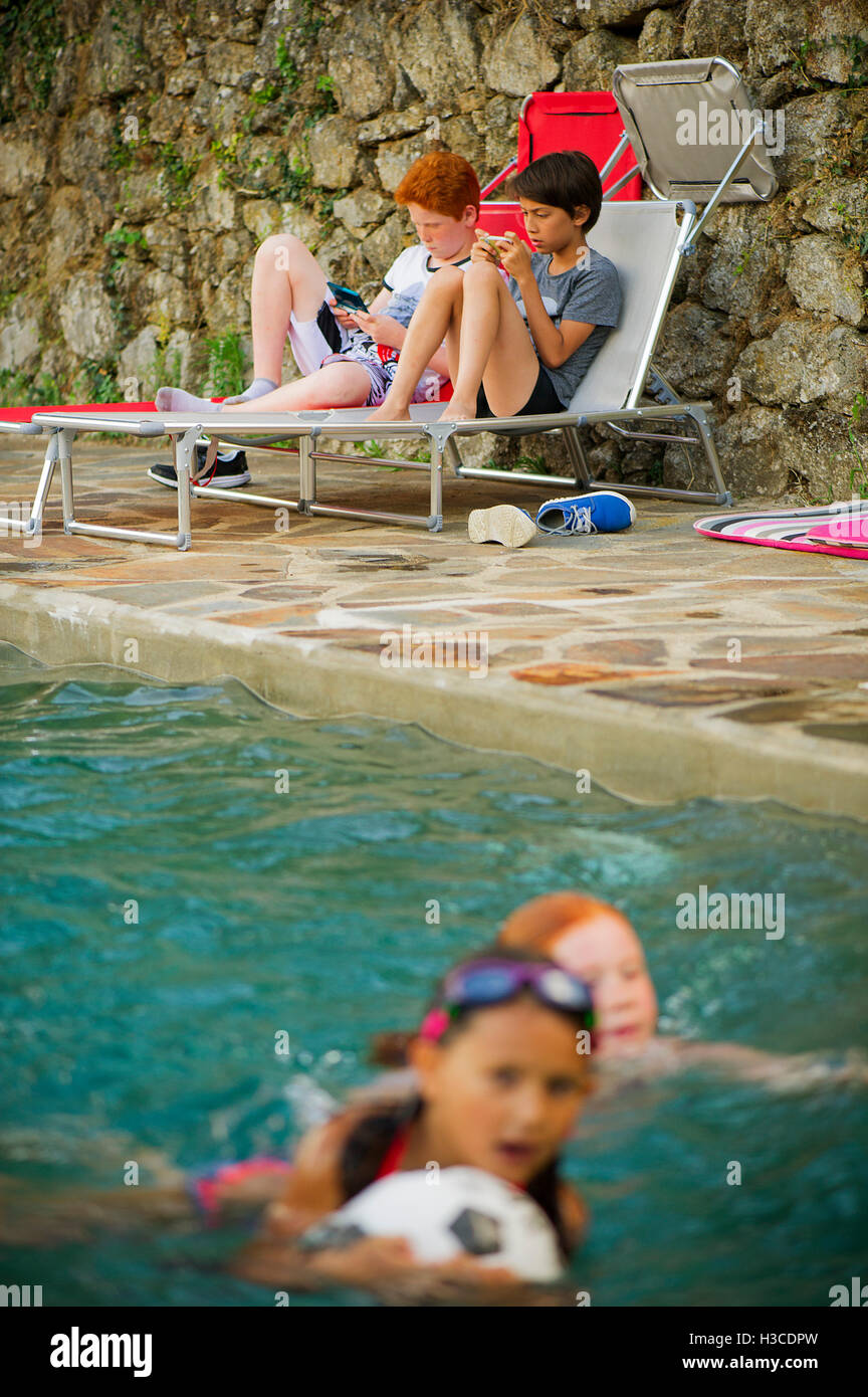 Boys playing handheld video games beside swimming pool - Stock Image
