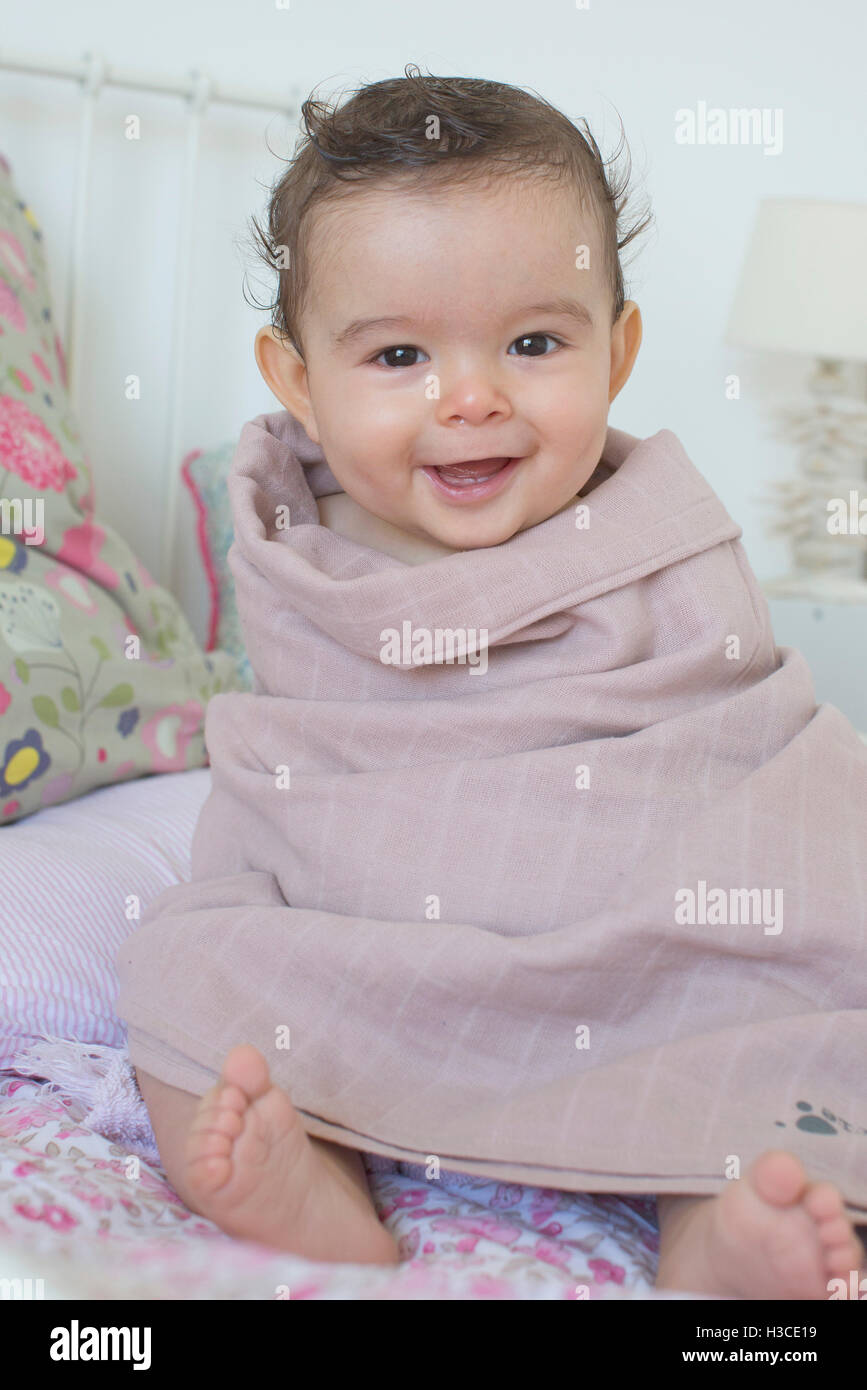 Baby wrapped in a towel, smiling, portrait - Stock Image