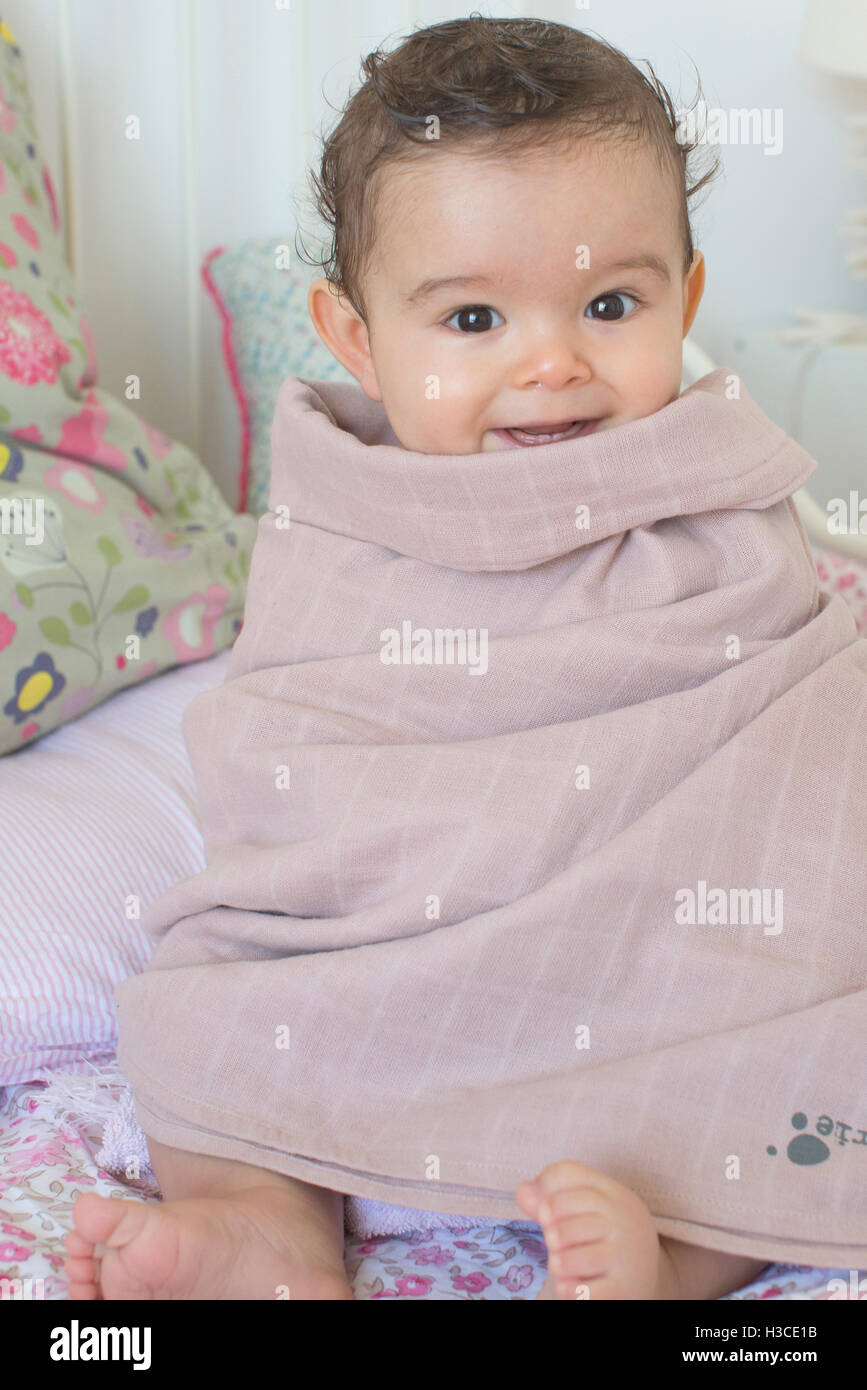 Baby wrapped in a towel after a bath, portrait - Stock Image