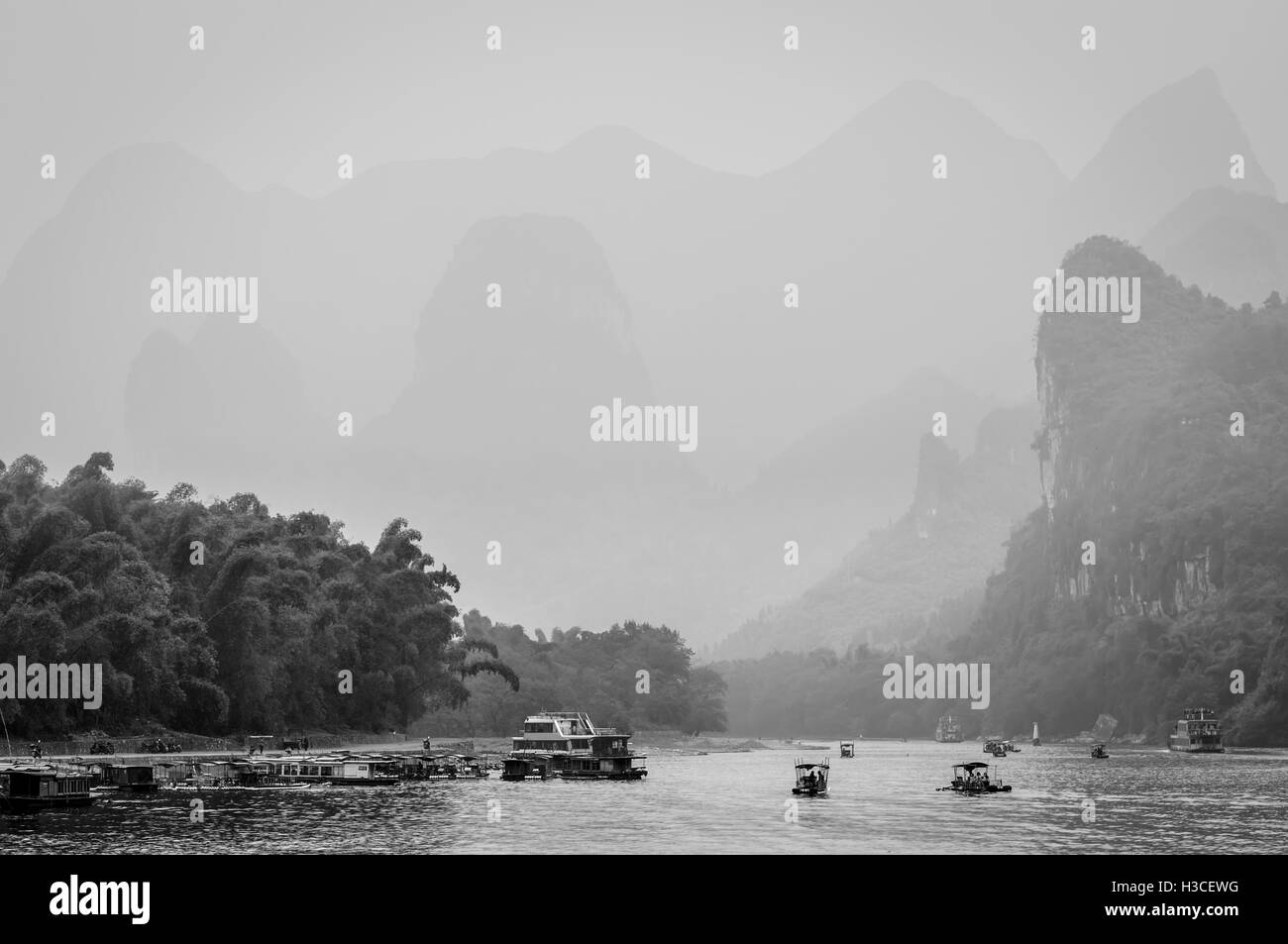 Cruise ship  and boats packed with tourists travels the magnificent scenic route in the haze along the Li river - Stock Image