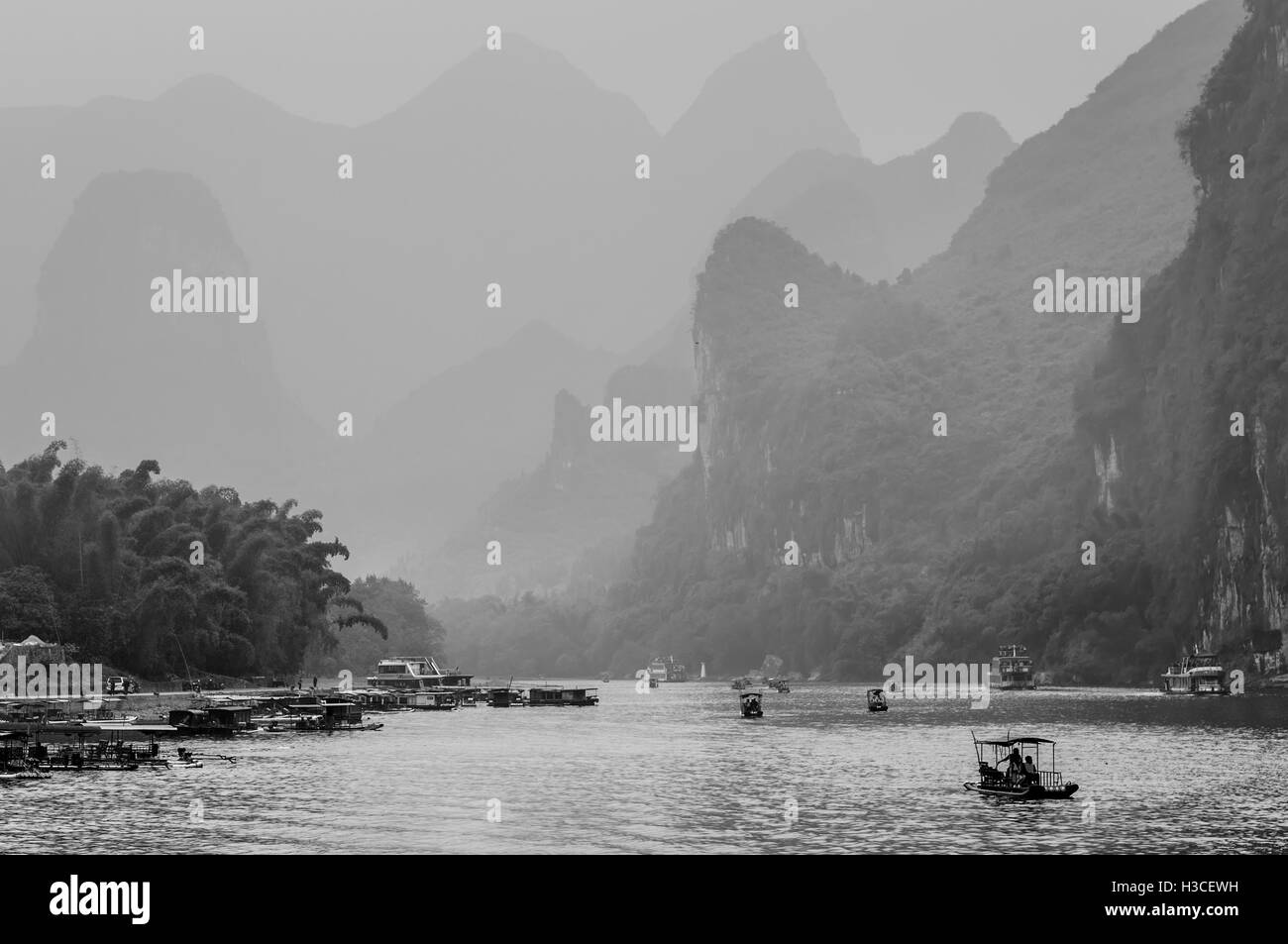 Cruise ship and boats packed with tourists travels the magnificent scenic route in the haze - Stock Image