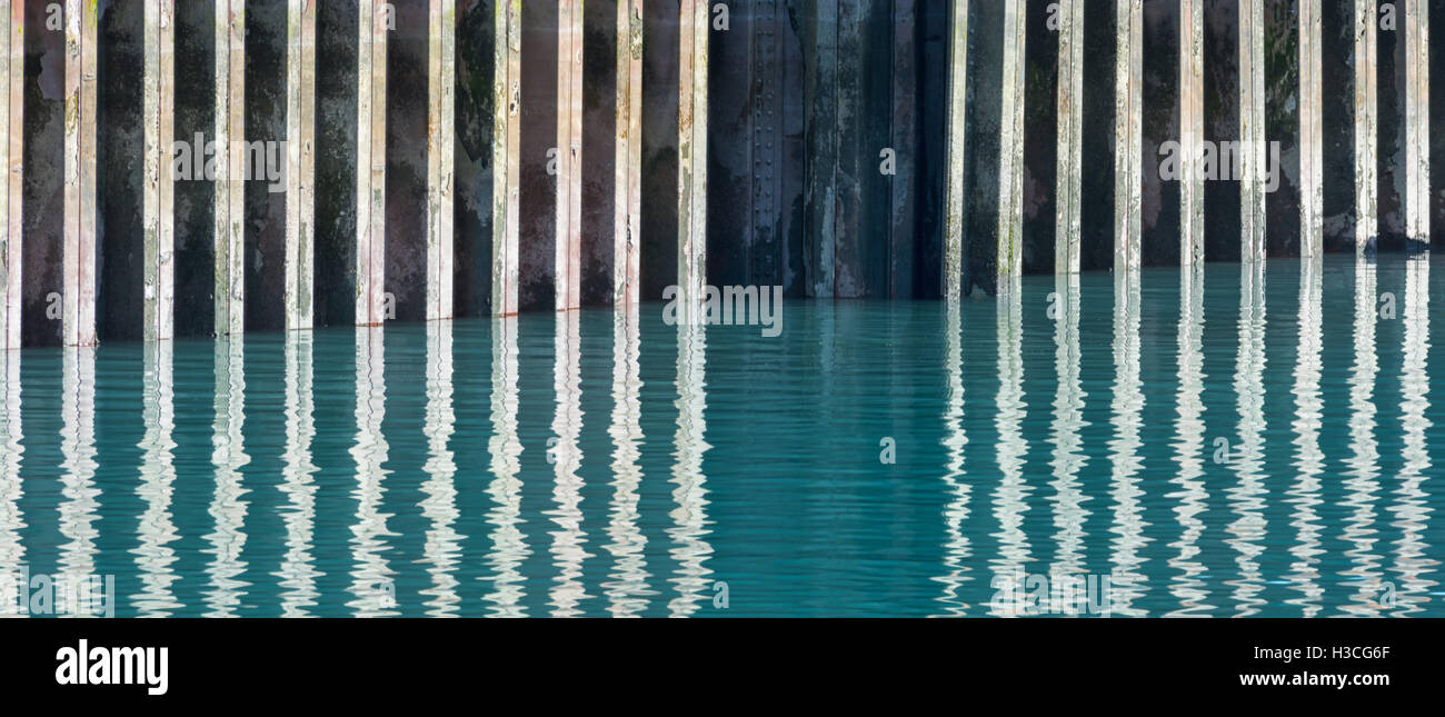 A support beam creates a break in the reflection of a metal seawall in the slightly rippled water. - Stock Image