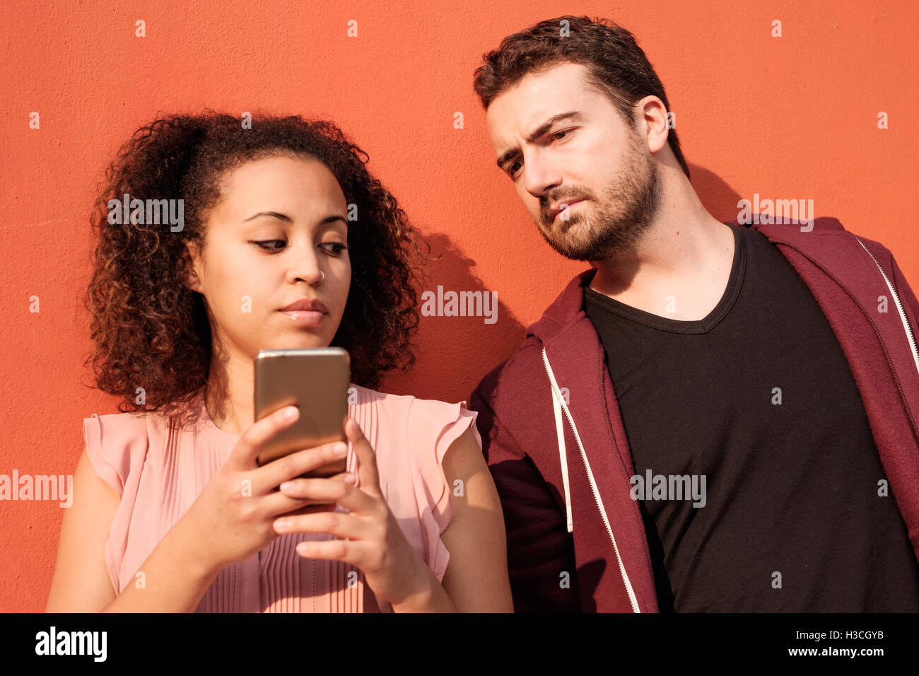 Man spying his girlfriend mobile phone - Stock Image
