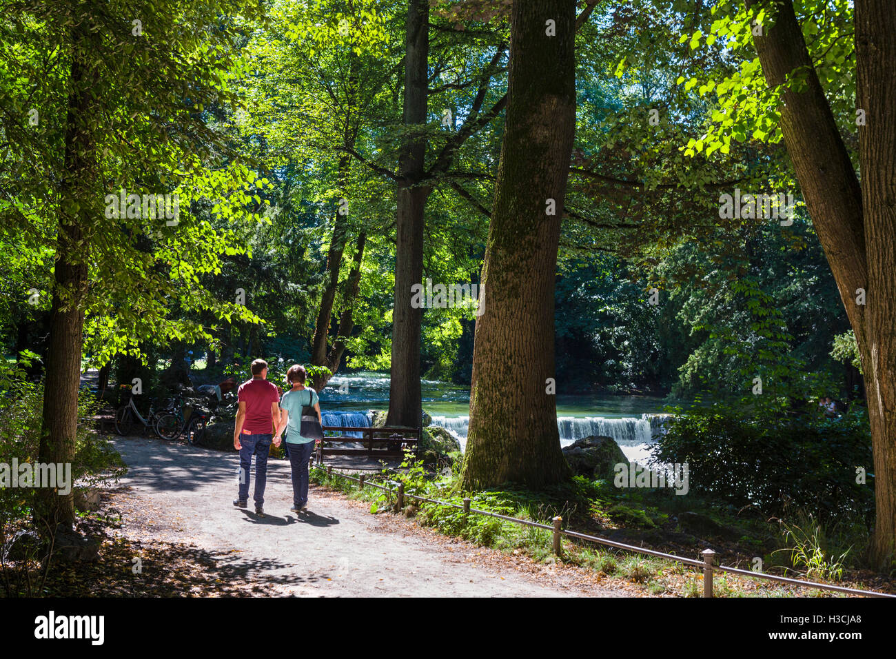 Couple by the Eisbach in the Englischer Garten, Munich, Bavaria, Germany - Stock Image