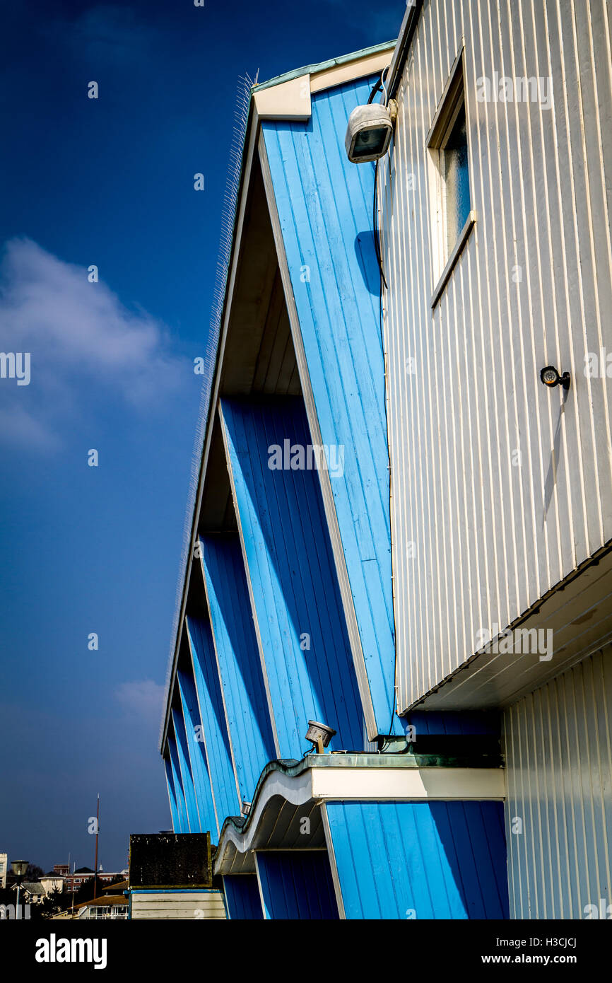 curves and angles on blue building with bright sky - Stock Image