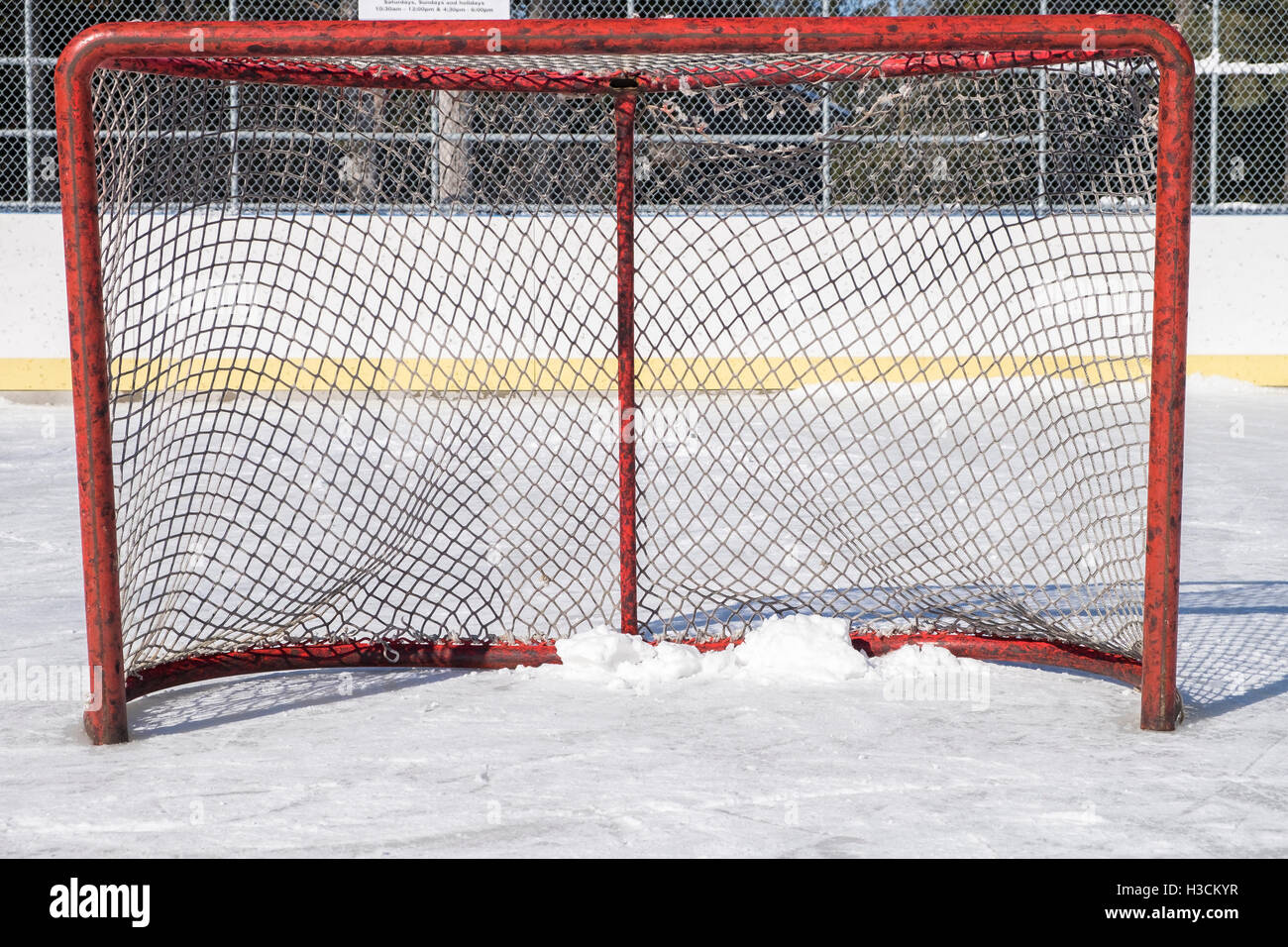 A close view of an ice hockey net it's posts black marked by pucks