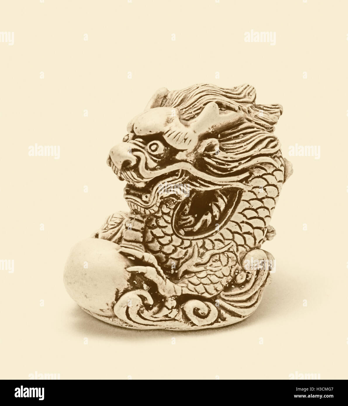 Netsuke of east dragon, which guarding the egg. A miniature sculpture, which was used as a button-like trinket in - Stock Image