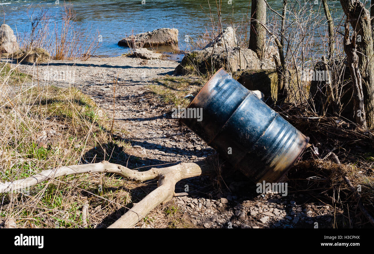 Partly rusted metal garbage can or drum leaning on branch on gravel path near river. - Stock Image
