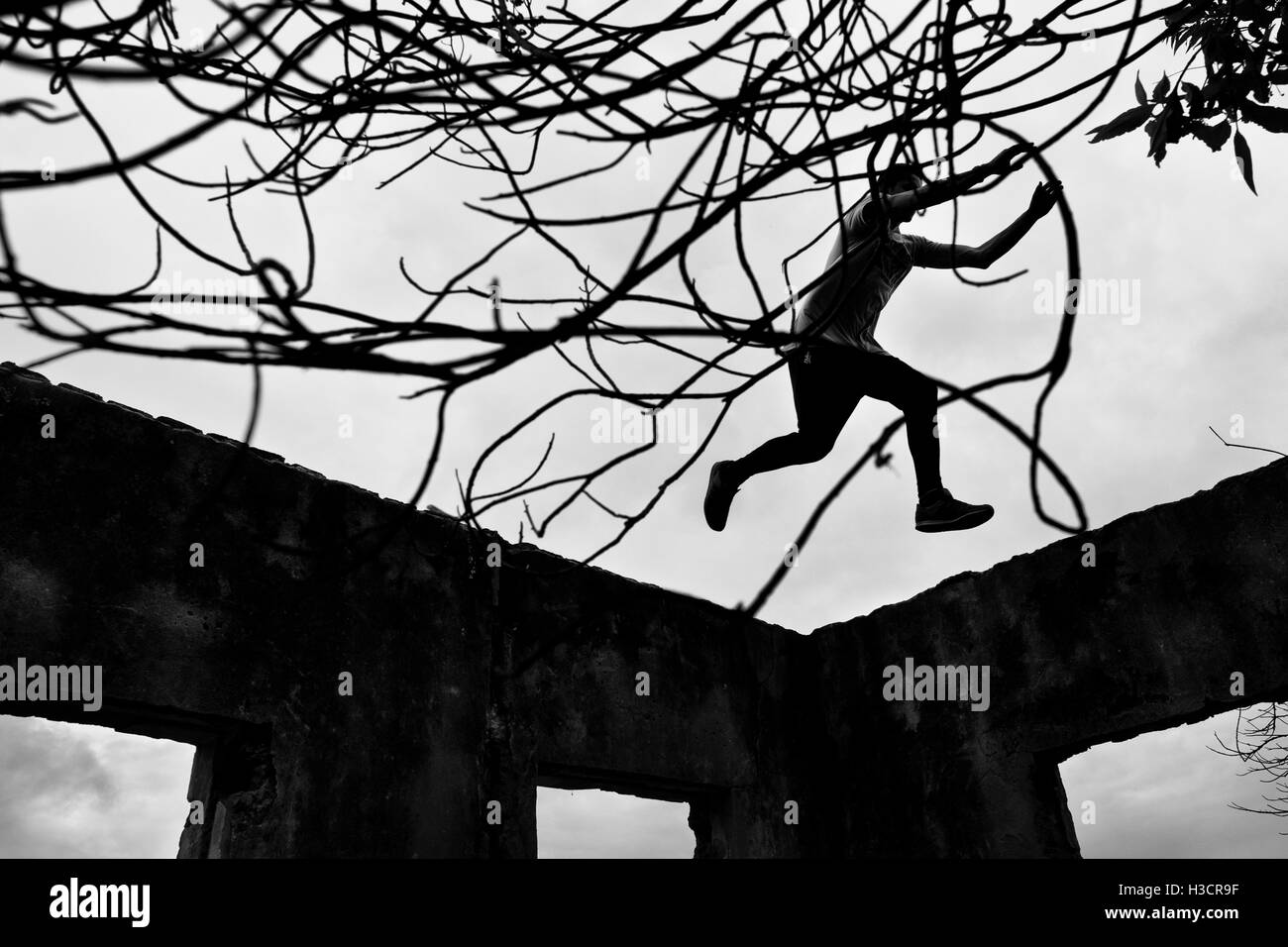 Jose Rodriguez, a freerunner from Plus Parkour team, jumps on the top of walls of an abandonned school in Bogotá, - Stock Image