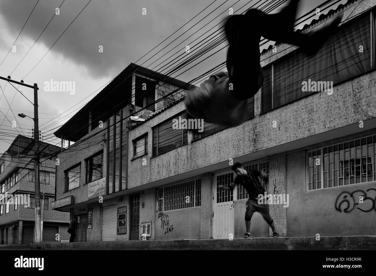 Colombian parkour athletes from Plus Parkour team do a front flip as they practise on the street in Bogotá, - Stock Image