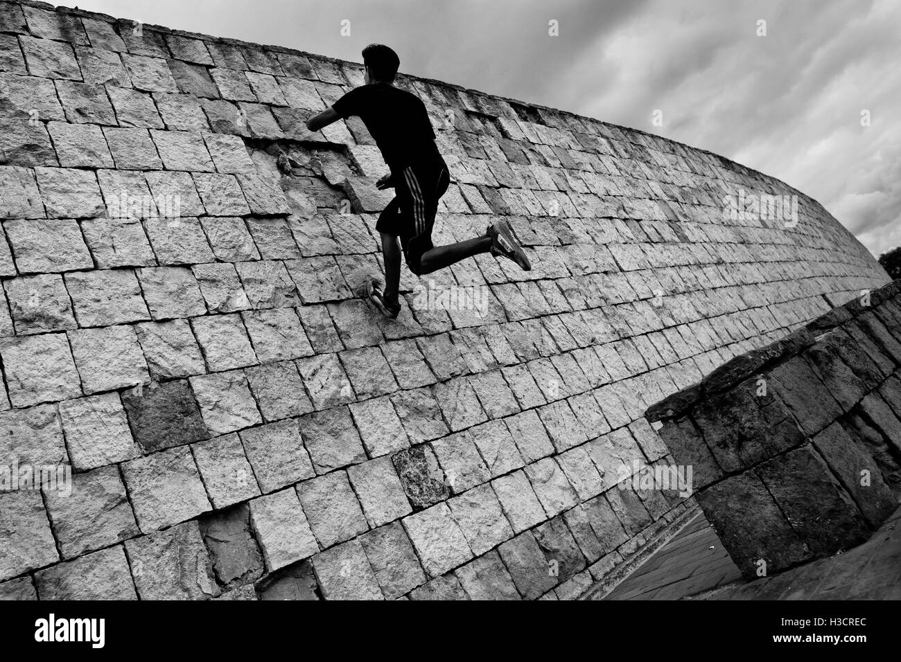 A Colombian parkour runner jumps on the wall during a free running training session in a park in Bogotá, Colombia. - Stock Image