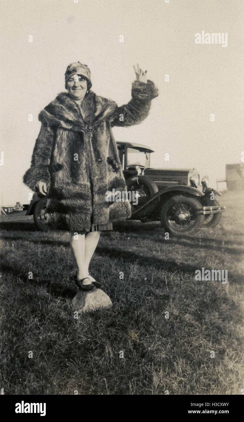 Antique c1930 photograph, woman in fur coat balances on rock near a Ford automobile. Location: Massachusetts, New - Stock Image