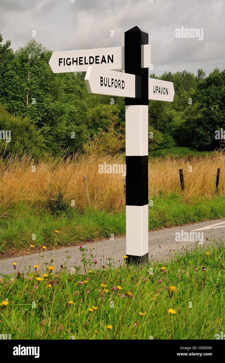A black and white signpost on a minor road. - Stock Image