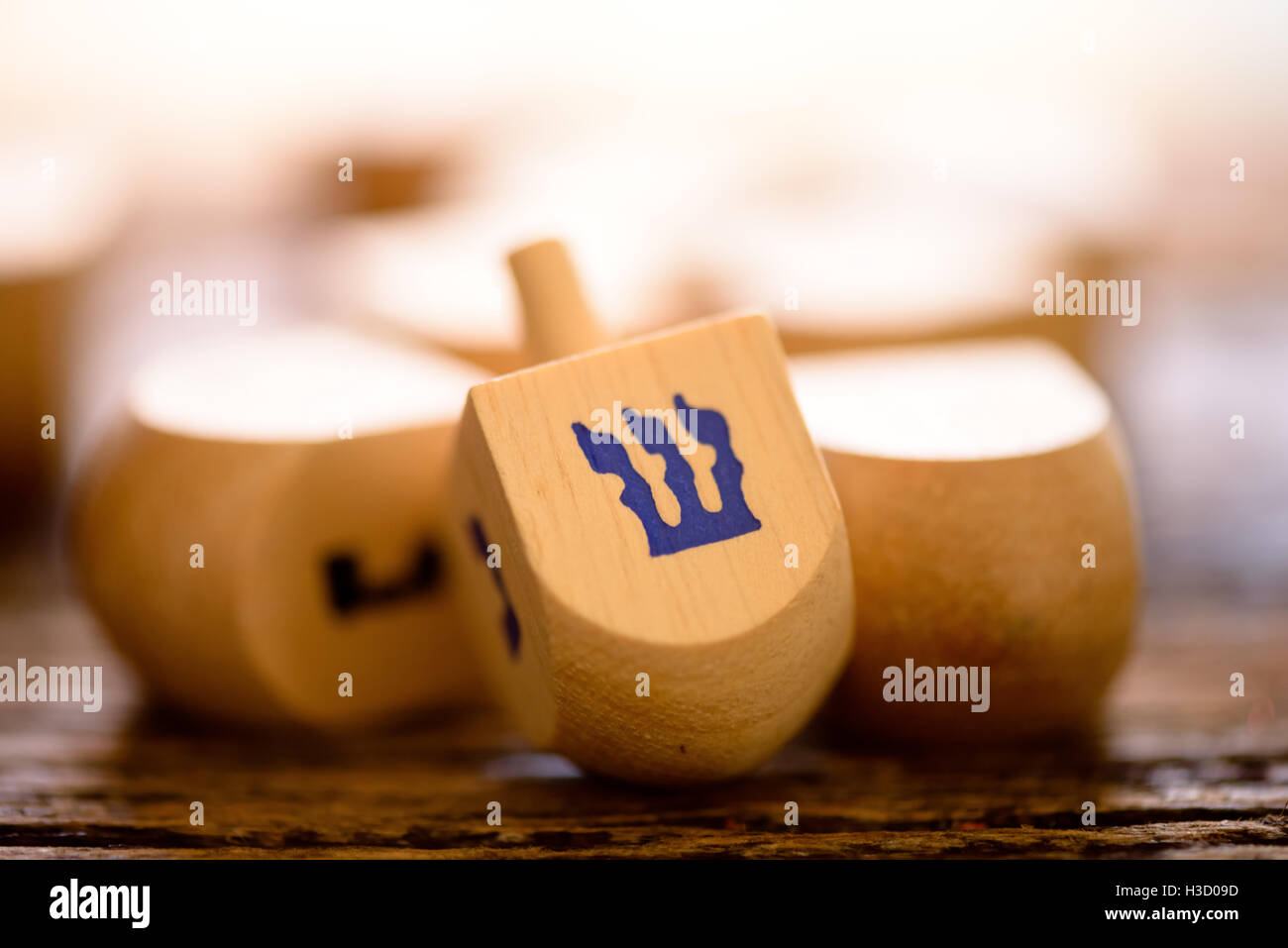 Arrangement of Jewish dreidels for Hanukkah set on rustic wood. - Stock Image