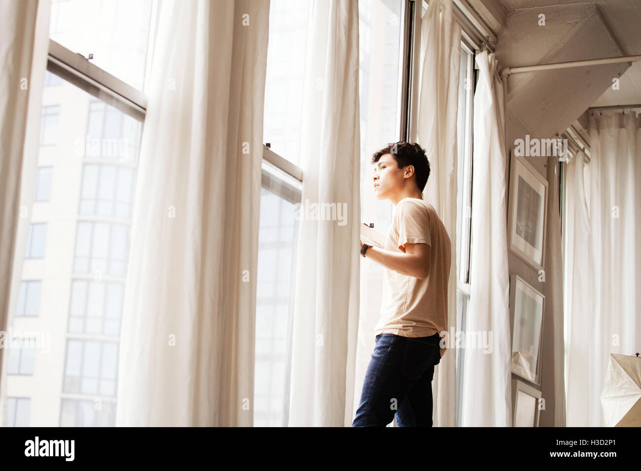 Side view of thoughtful man looking through window at home - Stock Image