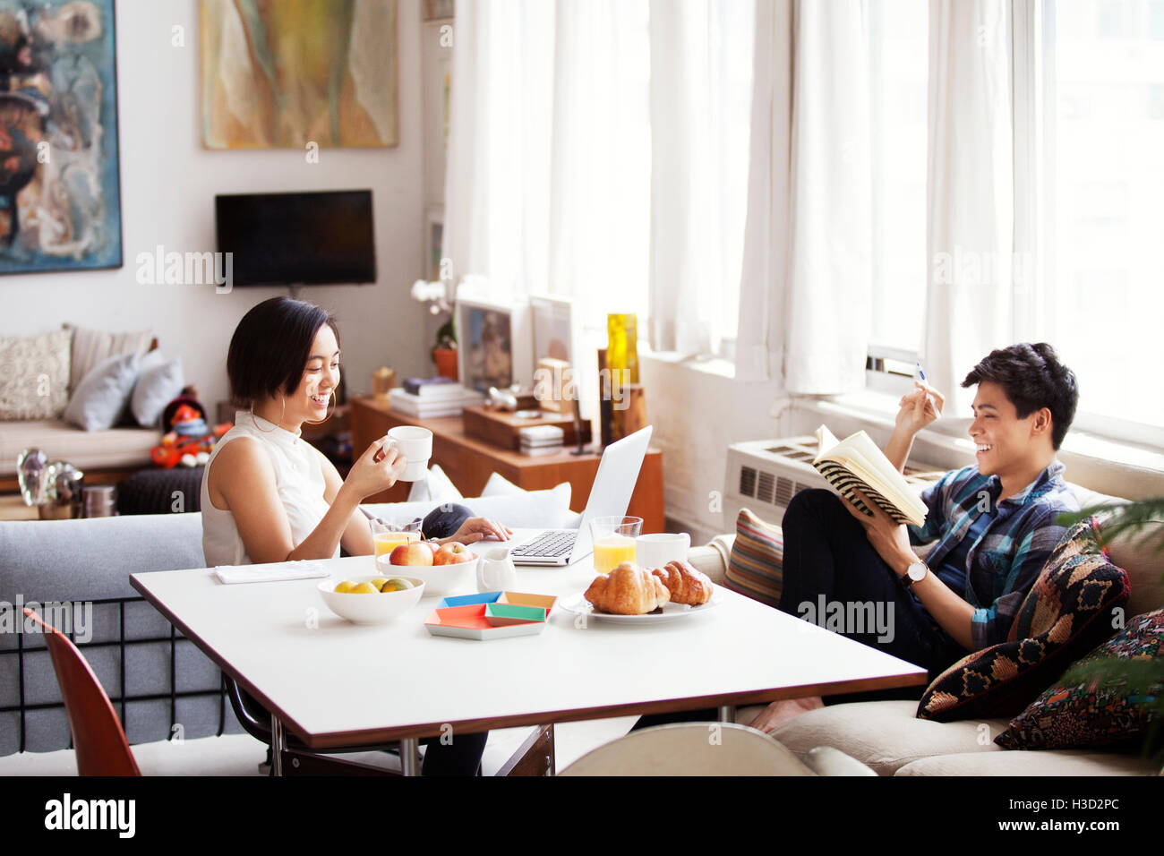 Happy couple spending leisure time in living room - Stock Image