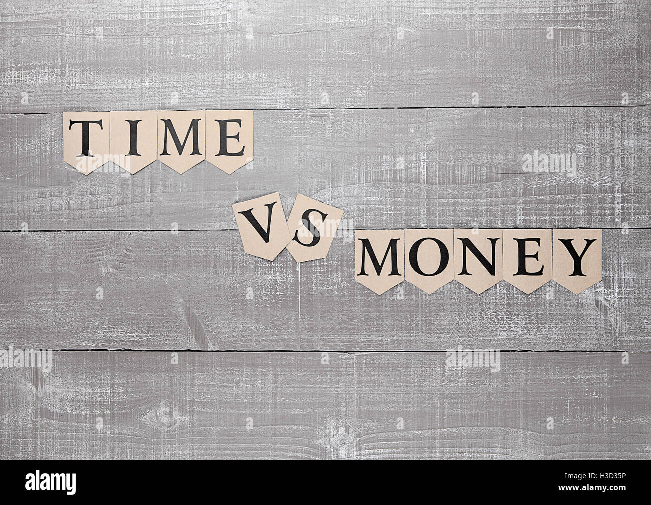 time vs money paper letters symbol motivation sign on wooden board Stock Photo