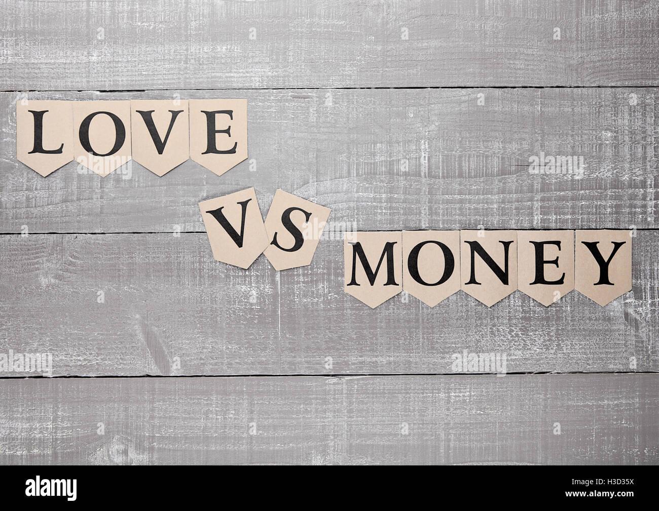 love vs money paper letters symbol motivation sign on wooden board - Stock Image