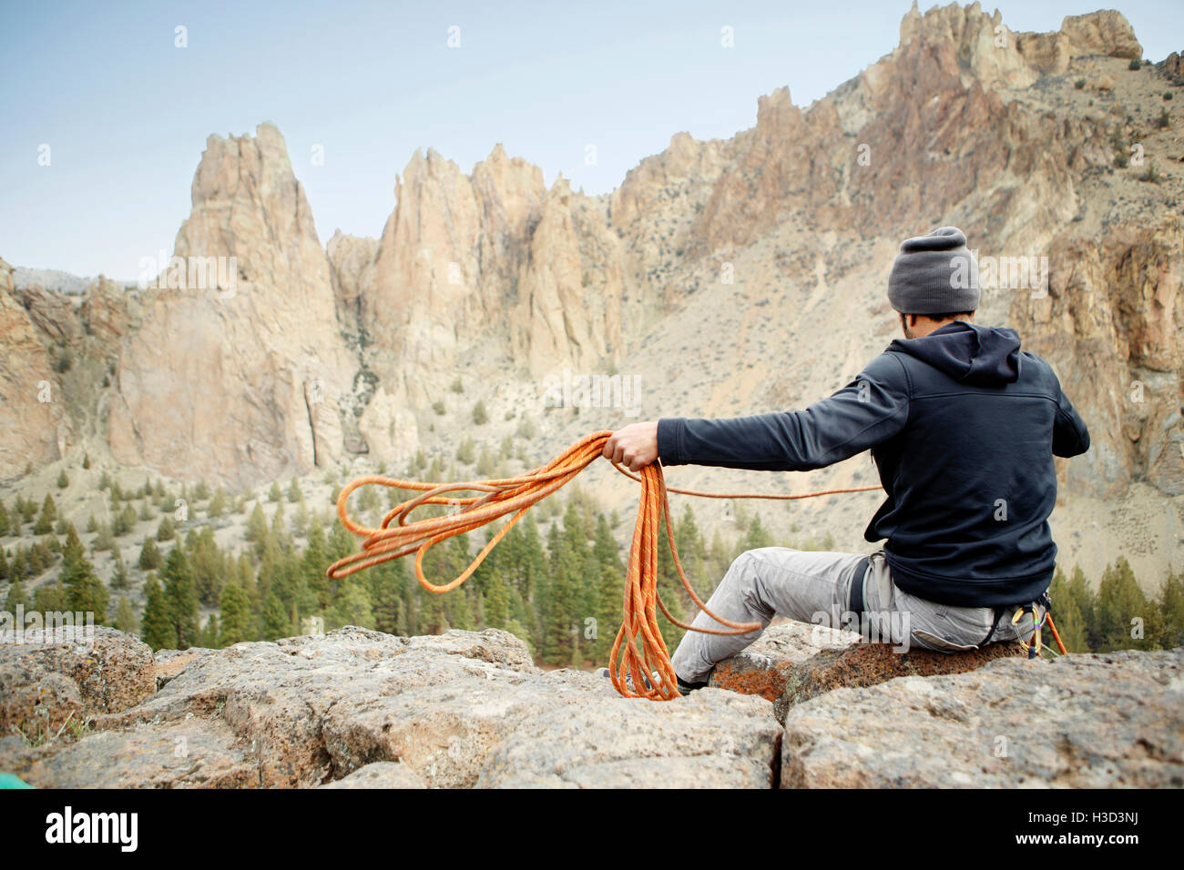Rear view of rock climber throwing rope while siting on mountain - Stock Image