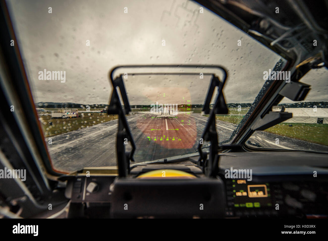Airplane on runway against sky seen through wet windshield - Stock Image