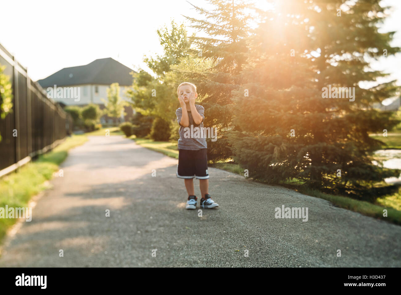Boredom boy standing on footpath by trees - Stock Image