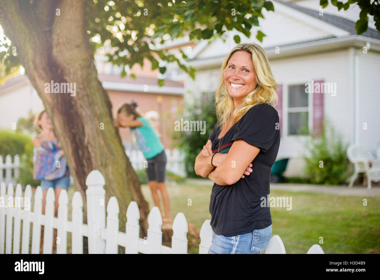 Happy woman looking away while children playing hide and seek in backyard - Stock Image