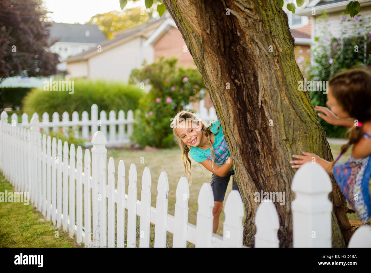Happy sisters playing hide and seek in backyard - Stock Image