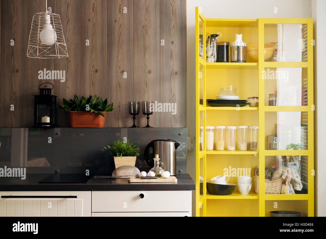Yellow cabinet by kitchen counter at home - Stock Image