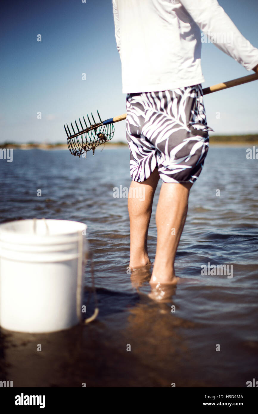 Low section of man holding clam rake at beach - Stock Image
