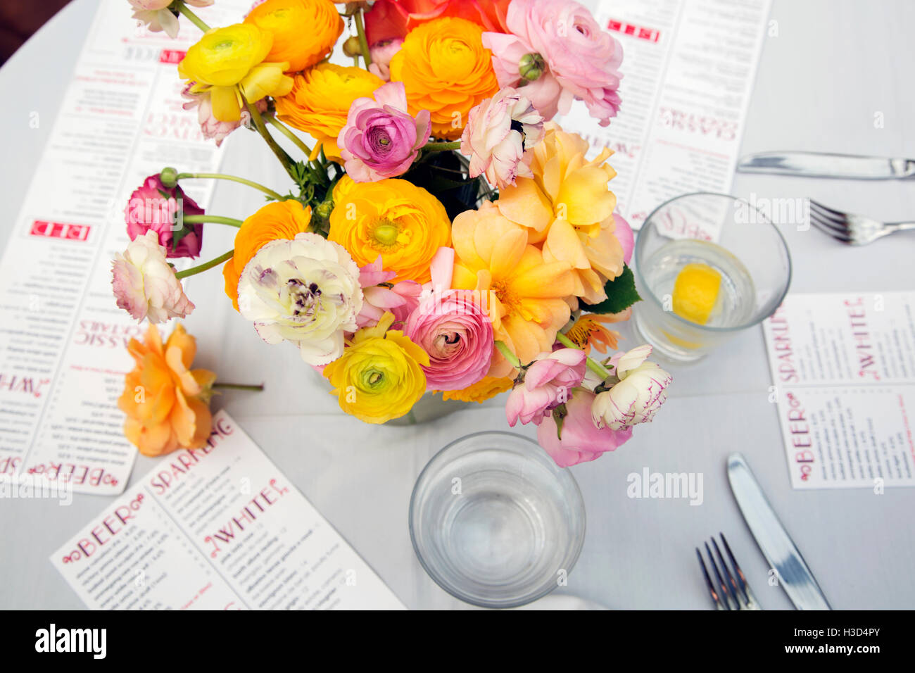 High angle view of flower vase with menus and water glasses on restaurant table - Stock Image