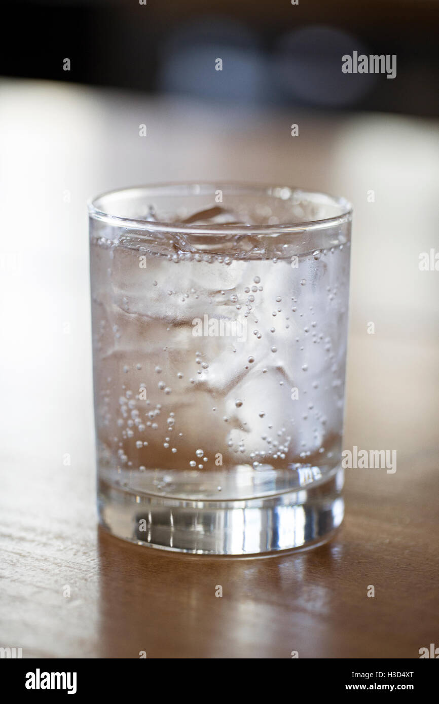 Close-up of carbonated water in glass on wooden table - Stock Image